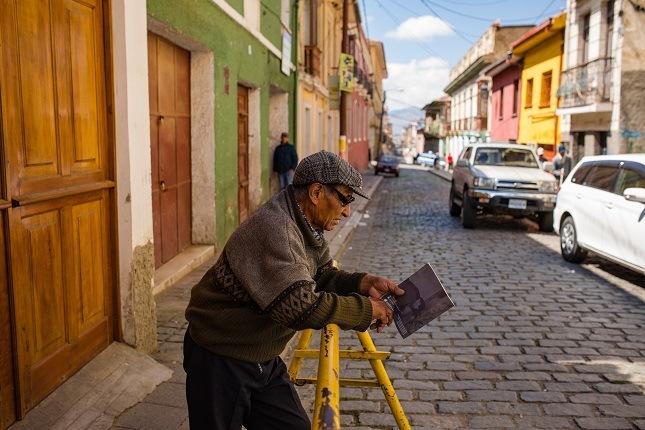 Ein alter Mann steht an einem Gitter gelehnt in einer der Straßen von La Paz. Im Hintergrund sind die bunten Häuser und die Berge zu sehen.