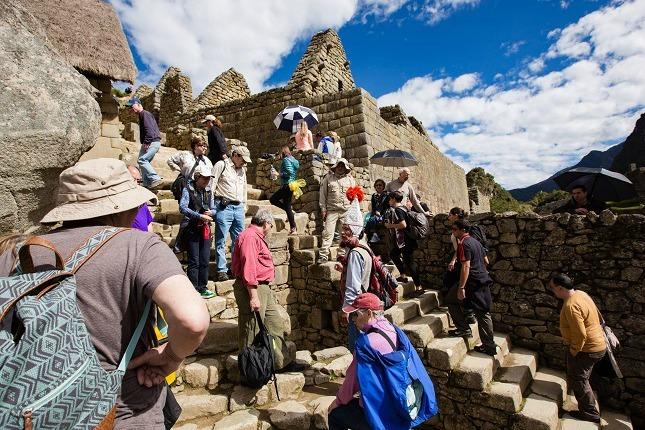 Touristen besichtigen die Ruinenstadt im Sonnenschein.