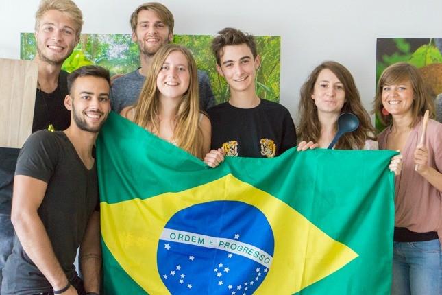 Das viventura Marketing Team hält die brasilianische Flagge hoch.